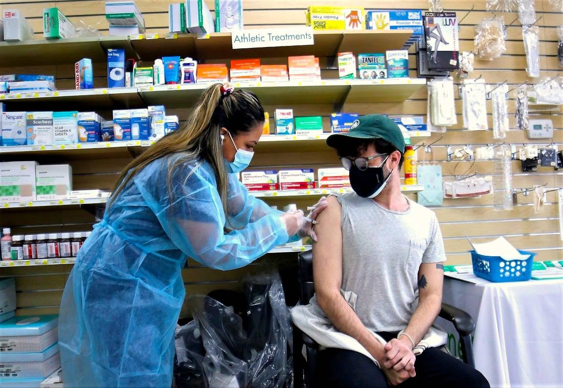 pharmacist vaccinating patient inside pharmacy - v 3