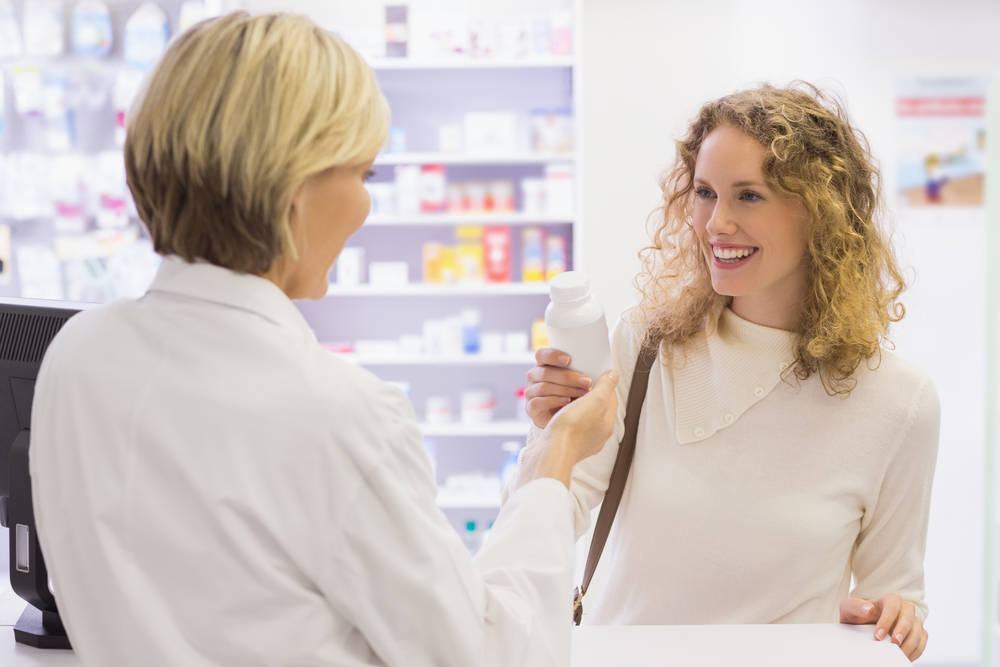 Smiling pharmacist and customer discussing a product in the pharmacy