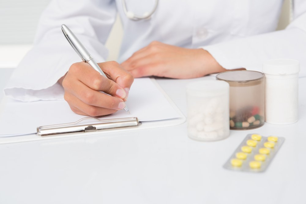 Vet writing on clipboard the prescriptions in medical office